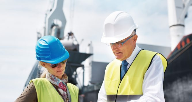 Two colleagues wearing hardhats and yellow vests while discussing a project.
