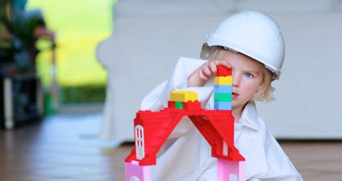Dziecko buduje wieżę z klocków